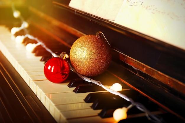 Klawisze fortepianu ozdobione ozdobnymi światłami i kulkami, z bliska