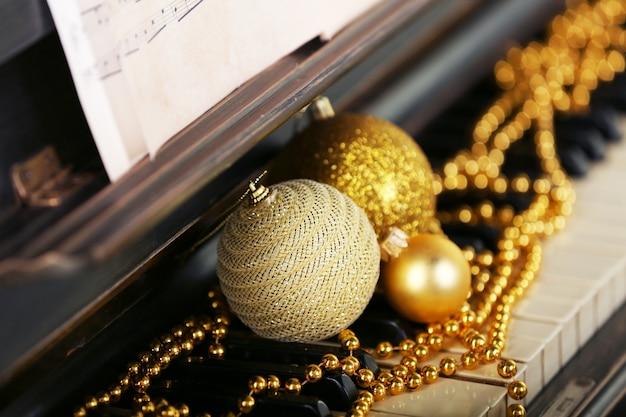 Klawisze fortepianu ozdobione złotymi dekoracjami świątecznymi, z bliska