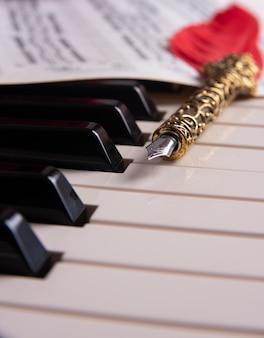 Klawisze fortepianu, pióro wieczne i partytura, selektywne skupienie.