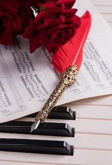 Klawisze fortepianu, wieczne pióro, nuty i bukiet róż, selektywne skupienie.