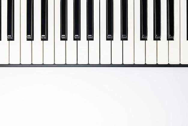 Klawisze fortepianu z miejsca kopiowania, na białym tle dla projektu, widok z góry, płaskie lay.