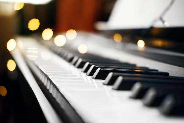 Klawisze fortepianu z pięknym żółtym światłem bokeh