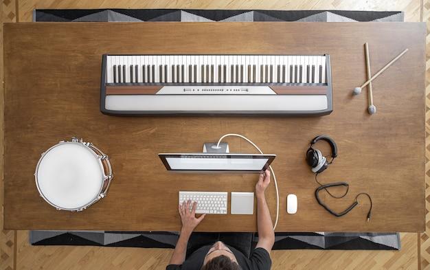 Klawisze muzyczne, kije, bęben, słuchawki i komputer na drewnianym stole. miejsce pracy muzyka do pracy nad dźwiękiem.