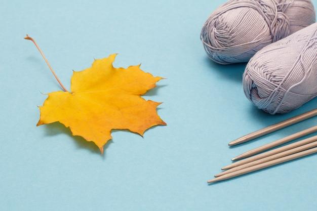 Kłębki przędzy dziewiarskiej, metalowe igły dziewiarskie i liść klonu na niebieskim tle. koncepcja dziania.