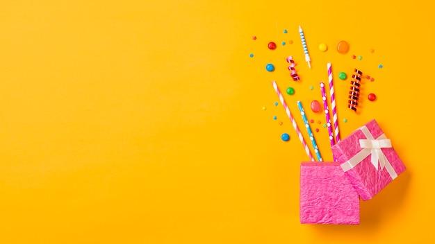 Klejnoty; słomki do picia; serpentyny; kropi z otwartego różowego pudełka na żółtym tle