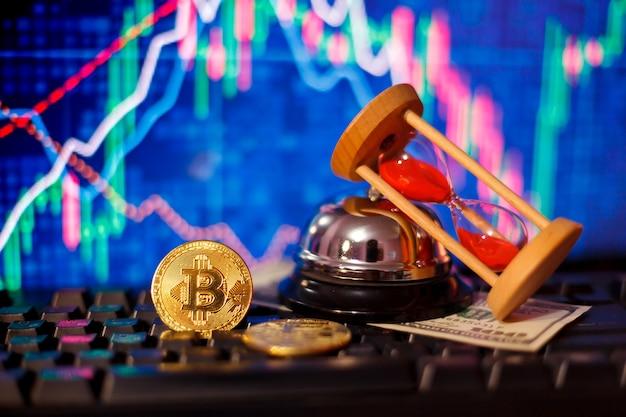 Klepsydra, dolary i bitcoiny na klawiaturze komputera na tle wykresów