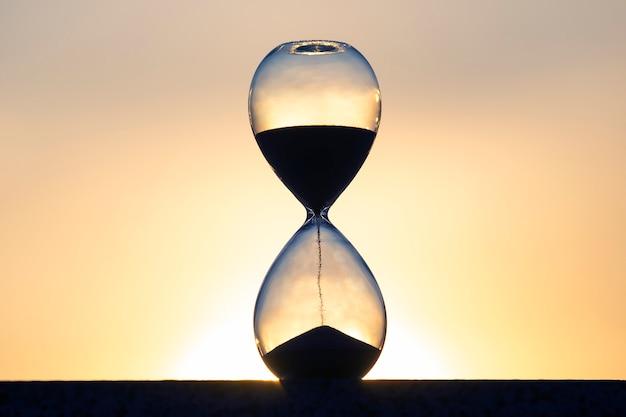 Klepsydra liczy czas na tle zachodzącego słońca