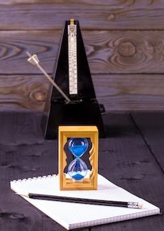 Klepsydra, metronom i notatnik z ołówkiem na drewnianym stole