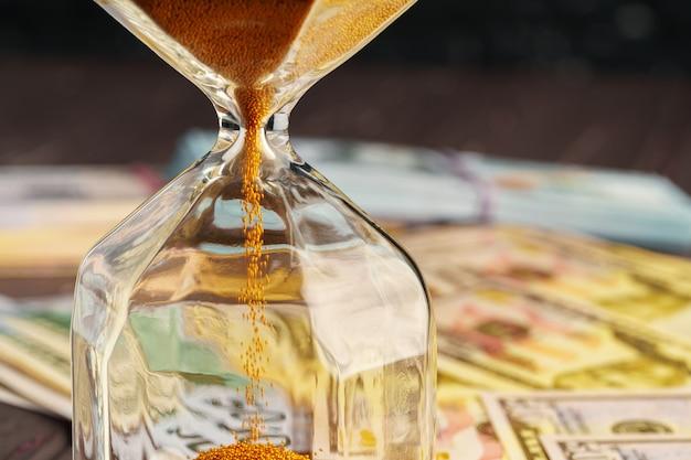 Klepsydra na stercie dolarowych banknotów zamyka up