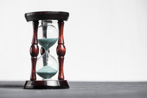 Klepsydra na szarym biurku pokazującym ostatnią sekundę lub ostatnią minutę lub limit czasu