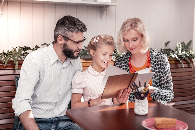 Klienci kawiarni. radosna pozytywna dziewczyna czytająca menu siedząc razem z rodzicami