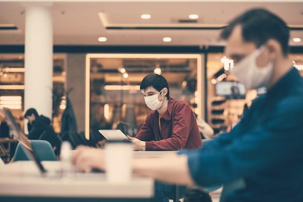 Klienci kawiarni w ochronnych maskach pracujący na swoich laptopach. higiena osobista i opieka zdrowotna