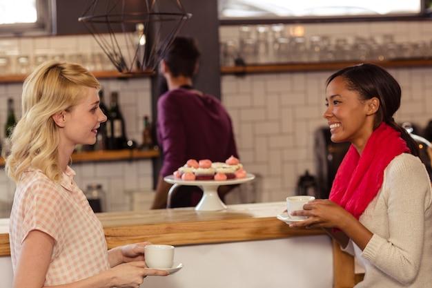 Klienci piją kawę z barmanem