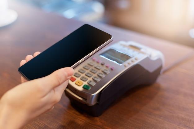 Klient bez twarzy płacący za pomocą technologii nfc