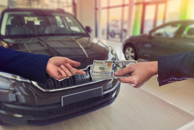 Klient dający nam sprzedawcę pieniędzy na sprzedaż lub wynajem nowego samochodu.