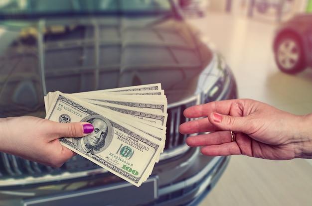 Klient Dający Nam Sprzedawcę Pieniędzy Na Sprzedaż Lub Wynajem Nowego Samochodu. Premium Zdjęcia