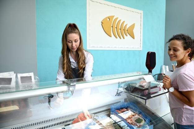 Klient dokonujący zakupu w sklepie z owocami morza. sprzedawca ryb wyjmujący z lodówki zapieczętowany stek z łososia i sprzedający go konsumentowi. sprzedaż detaliczna owoców morza.