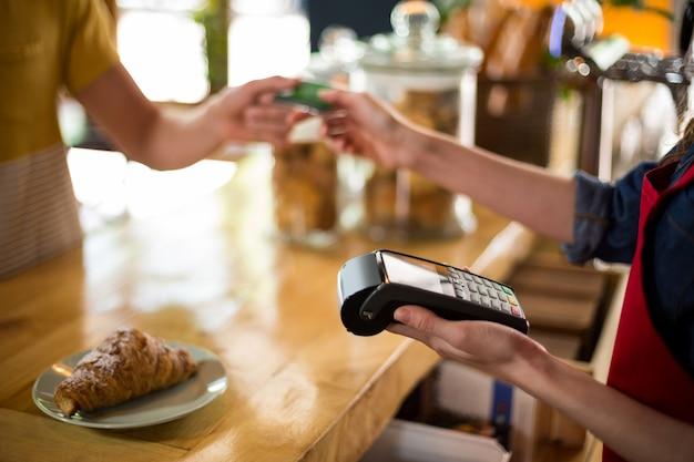Klient dokonuje płatności kartą kredytową w kasie w kawie