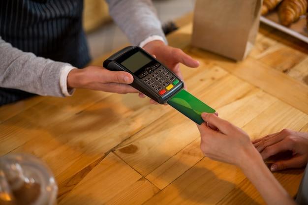 Klient dokonuje płatności za pomocą karty kredytowej w kasie