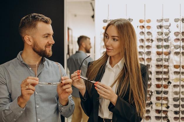 Klient dokonuje zakupu okularów w sklepie optycznym z pomocą sprzedawcy