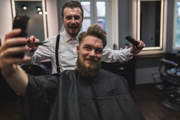 Klient i fryzjer pozuje dla selfie