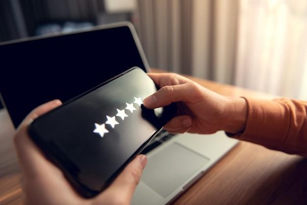 Klient kobieta trzymając się za ręce smartfona oceń swoje wrażenia, dając pozytywne opinie, kwestionariusz lub badanie satysfakcji klienta.