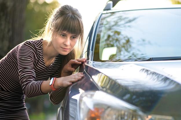 Klient młoda kobieta dokładnie bada nowy samochód w sklepie na świeżym powietrzu sprzedawcy przed zakupem.
