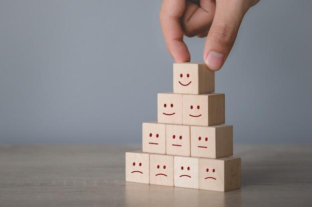Klient naciska smiley twarzy emoticon na drewnianym sześcianie, usługa ocena, satysfakci pojęcie.