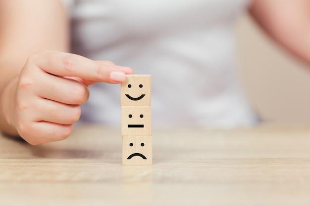 Klient naciskając emotikon emotikon na sześcian drewna