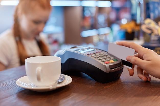 Klient płacący kartą za filiżankę kawy