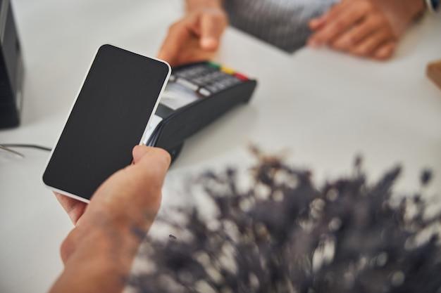 Klient płacący za zakup za pomocą telefonu