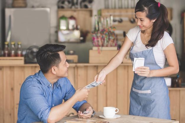 Klient płaci gotówką w kawiarni