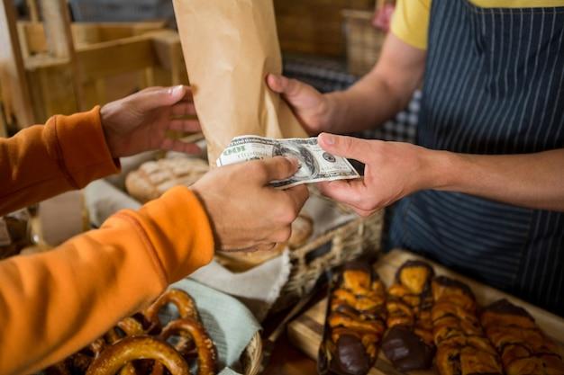 Klient płaci rachunek gotówką w kasie chleba