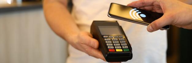 Klient płaci rachunek za pomocą telefonu komórkowego