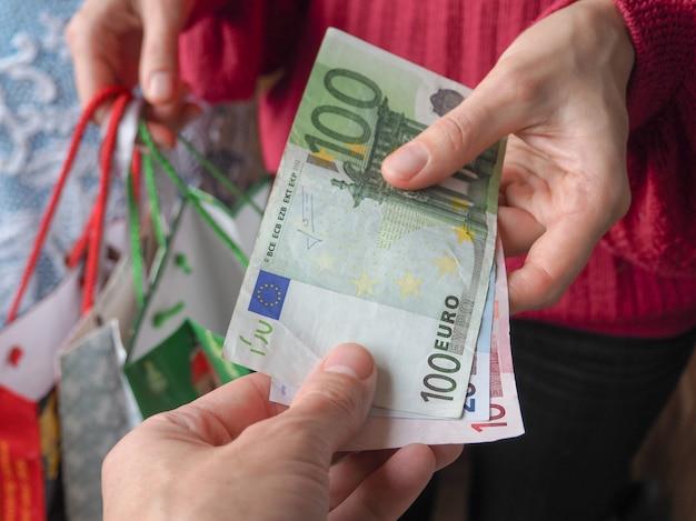Klient płaci rachunki w euro gotówką podczas zakupów.