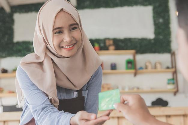 Klient płaci rachunki za pomocą karty kredytowej