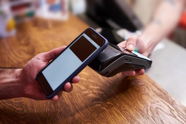 Klient płaci smartfonem z technologią nfc