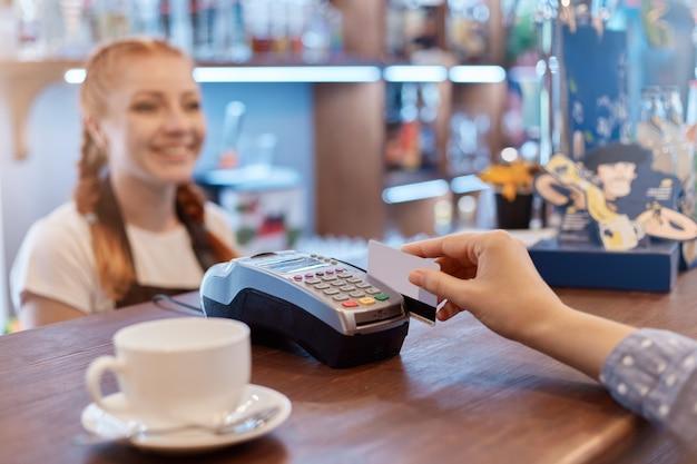 Klient płaci telefonem komórkowym przez czytnik elektroniczny w kawiarni