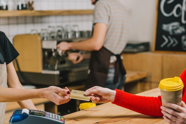 Klient płaci za napój w kawiarni