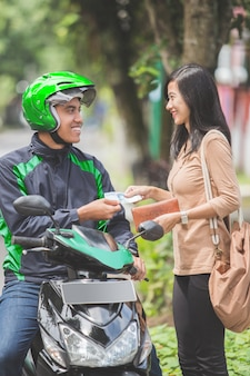 Klient płaci za przejazd taksówkarzem motocyklowym