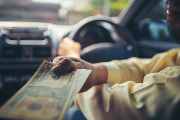 Klient płaci za taksówkę. płatności gotówkowe w transporcie