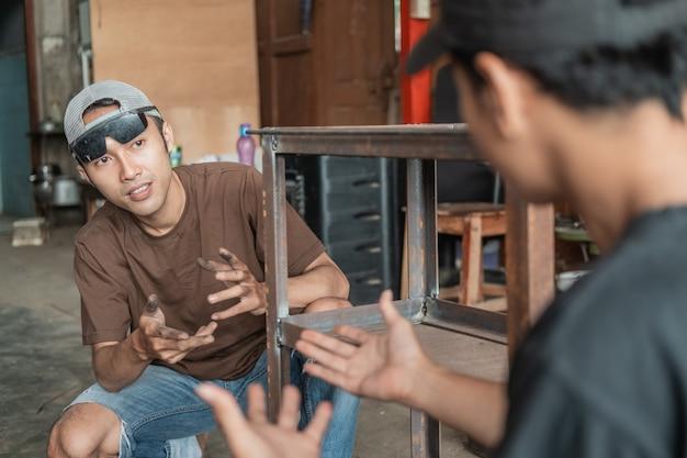 Klient płci męskiej rozmawia ze spawaczem gestem ręki w spawalni