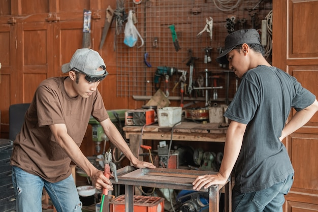 Klient płci męskiej widzi spawacza pracującego na metalowym stojaku w warsztacie spawalniczym