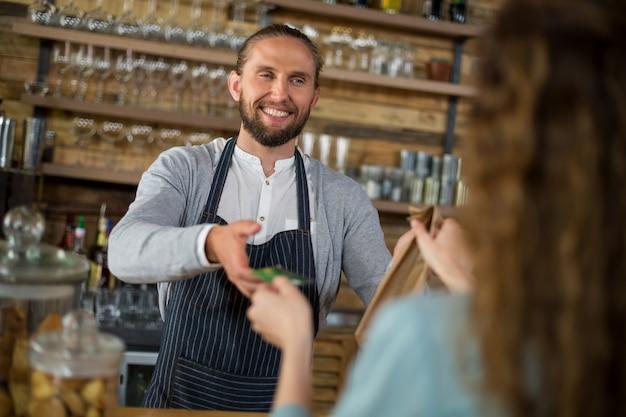 Klient podający kartę kredytową kelnerce przy odbiorze paczki w kasie