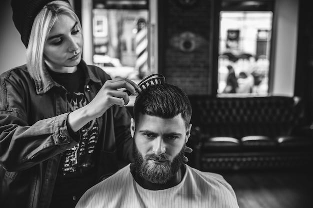 Klient podczas golenia brody u fryzjera młody przystojny fryzjer i atrakcyjny brodaty mężczyzna