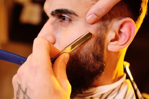 Klient podczas golenia brody w sklepie fryzjerskim