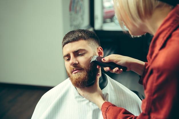 Klient podczas golenia brody w zakładzie fryzjerskim. kobieta fryzjer w salonie. równość płci. kobieta w męskim zawodzie.