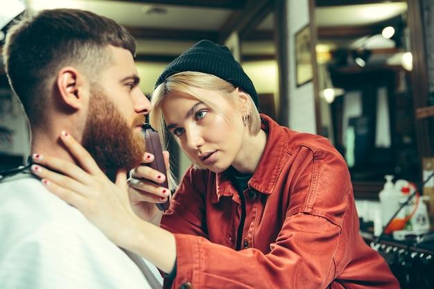 Klient podczas golenia brody w zakładzie fryzjerskim. kobieta fryzjer w salonie. równość płci