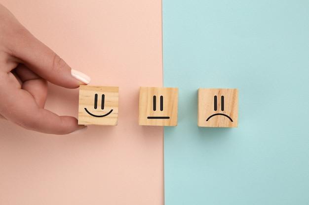 Klient pokazuje ocenę z szczęśliwą ikoną na kolorowym tle, koncepcja badania satysfakcji klienta, miejsce na kopię.
