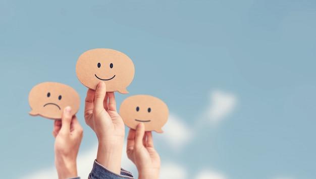Klient pokazuje ocenę z szczęśliwą ikoną na nieba tle, klient satysfakci ankiety pojęcie, kopii przestrzeń.
